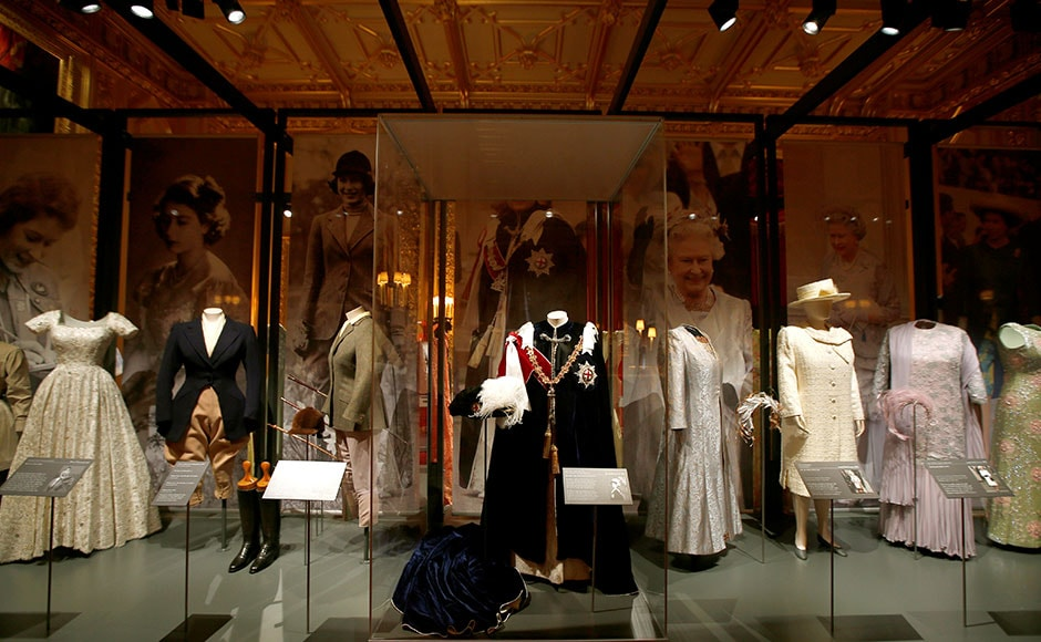 The gown worn by Britain's Queen Elizabeth during the annual Royal Garter Ceremony is seen on a mannequin alongside other outfits, in the State Dining Room at Windsor Castle in Windsor, Britain. Reuters