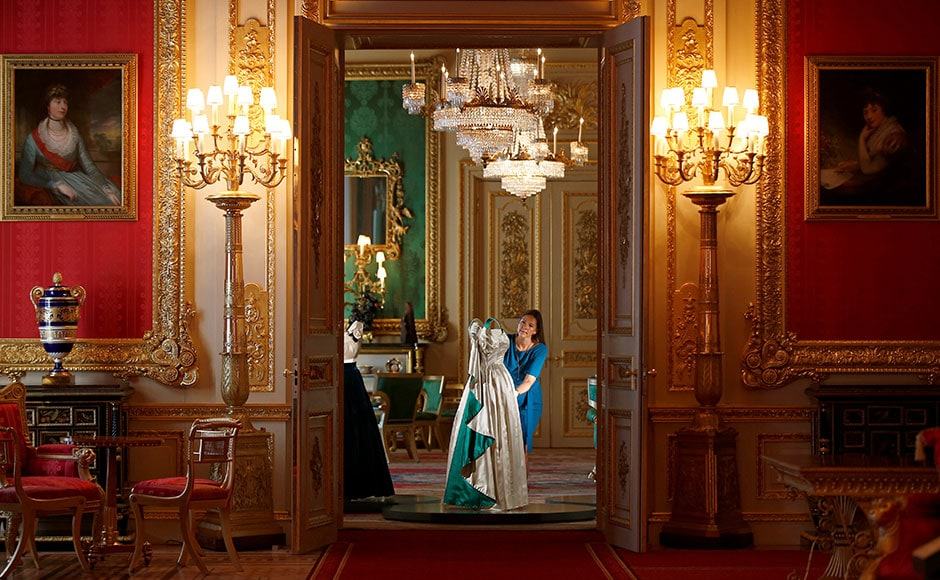 Curator Caroline de Guitaut, poses with an evening gown worn by Britain's Queen Elizabeth, in the Green Drawing Room. Reuters