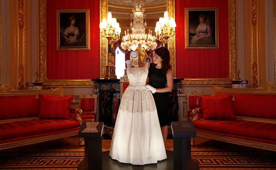 The exhibition 'Fashioning a Reign: 90 Years of Style from The Queen's Wardrobe', will show at the castle from 17 September, 2016 to 8 January, 2017. A member of staff of the Royal Collection poses with a dress worn by Britain's Queen Elizabeth. Reuters