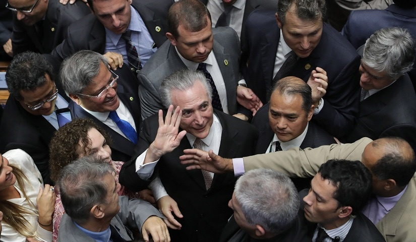 Brazil's President Michel Temer, center, is surrounded by senators as he arrives to take the presidential oath at the National Congress, in Brasilia, Brazil, Wednesday, Aug. 31, 2016. Temer was sworn in as Brazil's new leader following the ouster of President Dilma Rousseff. (AP Photo/Eraldo Peres)