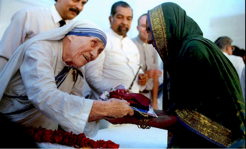 A file image of Mother Teresa presenting documents for a new house to a villager from Latur in Mumbai. Reuters
