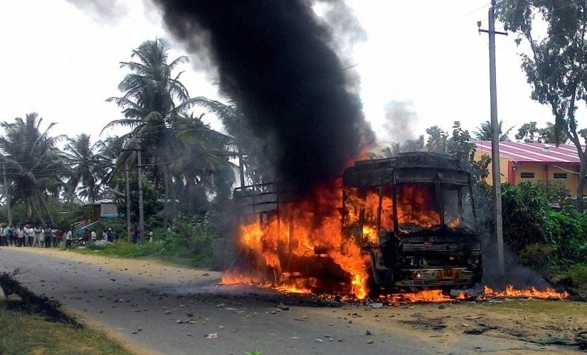 A vehicle in flames after it was torched by pro-Kannada activists during a protest over Cauvery water row, in Mandya district on Monday. PTI