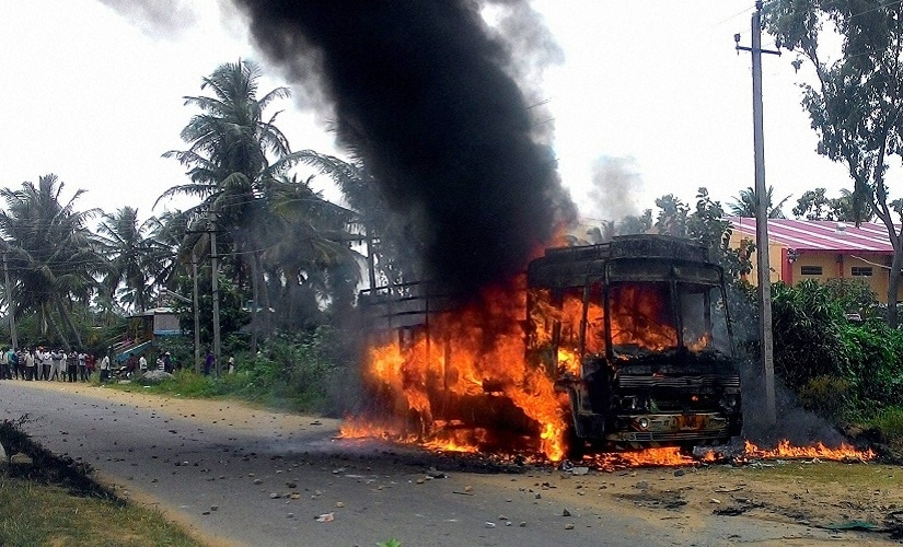 A vehicle in flames after it was torched by pro-Kannada activists during a protest over Cauvery water row, on Monday. PTI