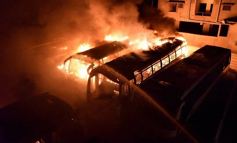 TN-bound buses in flames after they were torched by pro-Kannada activists during a protest over the Cauvery water row, on Monday. PTI