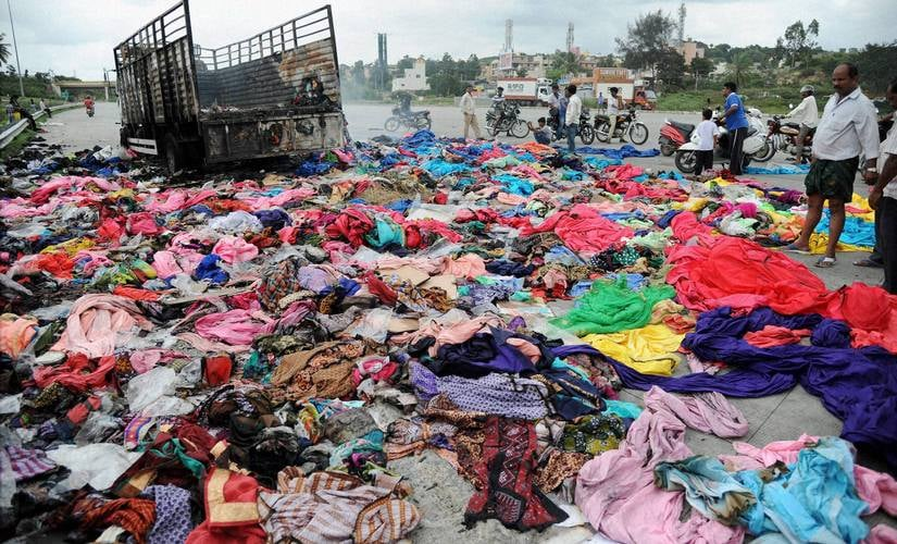 People collect valuable remains from a Tamil Nadu Goods truck that was set on fire by the protesters during protests over Cauvery issue, at Nice Road in Bengaluru on Tuesday. PTI