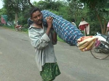 Dana Majhi carrying his wife on his shoulder. PTI