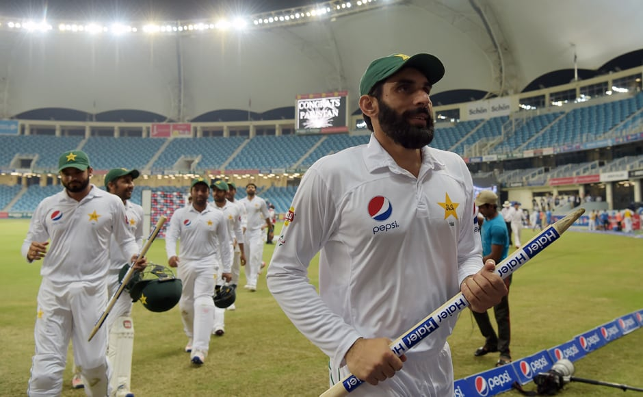 Pakistan captain Misbah-ul-Haq and his teammate Azhar Ali who scored a triple century in the first innings hold the wickets as they head back to the pavilion after defeatin West Indies by 56 runs. AFP