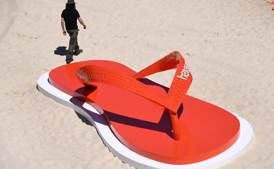 The event celebrated its 20th anniversary this year. A man walks past a giant jandal on Tamarama Beach. Photo: AFP