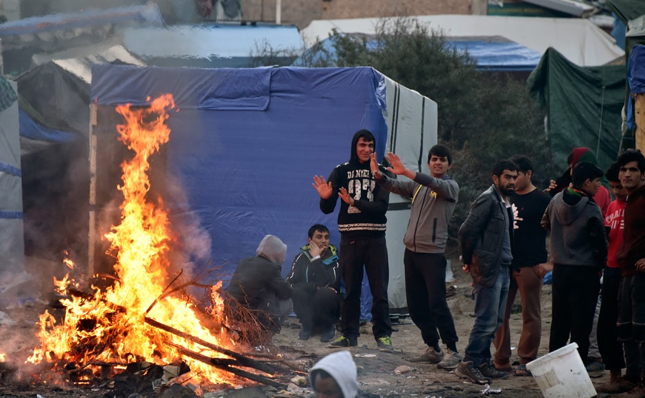 "The French government has started clearing the ""Jungle"" migrant camp on France's norther coast. Migrants, primarily from Africa and Middle East, used to live there. They try to warm themselves while waiting to be relocated. Photo: AFP"