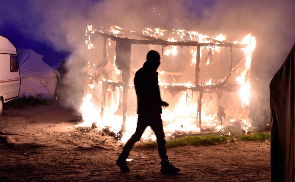 "The ""Jungle"" is a collection of tents and shelters patched together. They were burnt down by the authorities during the clearing operation. A migrant walks past a shack set on fire during the demolition of the camp. Photo: AFP"