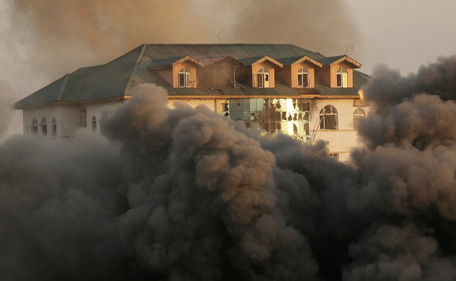Smoke and dust engulfed the building of Jammu and Kashmir Entrepreneurship Development Institute (JKEDI) where suspected militants have taken refuge. Photo: AP