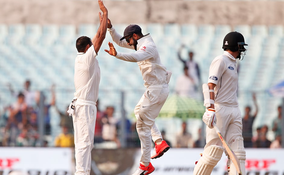 Indian bowler Mohammed Shami celebrates with captain Virat Kohli after taking the wicket of New Zealand's Mitchell Santner, right, on the fourth day of the second cricket test match in Kolkata, India, Monday, Oct. 3, 2016. AP
