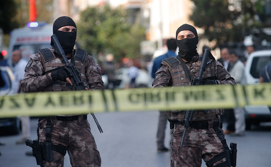 Masked police officers cordon off the area of a blast in Istanbul, A bomb placed on a motorcycle has exploded near a police station Thursday, wounding several people, Vasip Sahin, the governor for Istanbul, said. AP