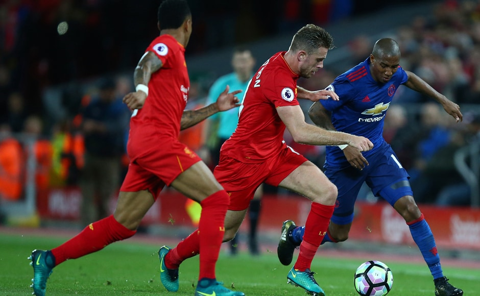 Liverpool's Jordan Henderson challenges for the ball with Manchester United's Ashley Young. AP