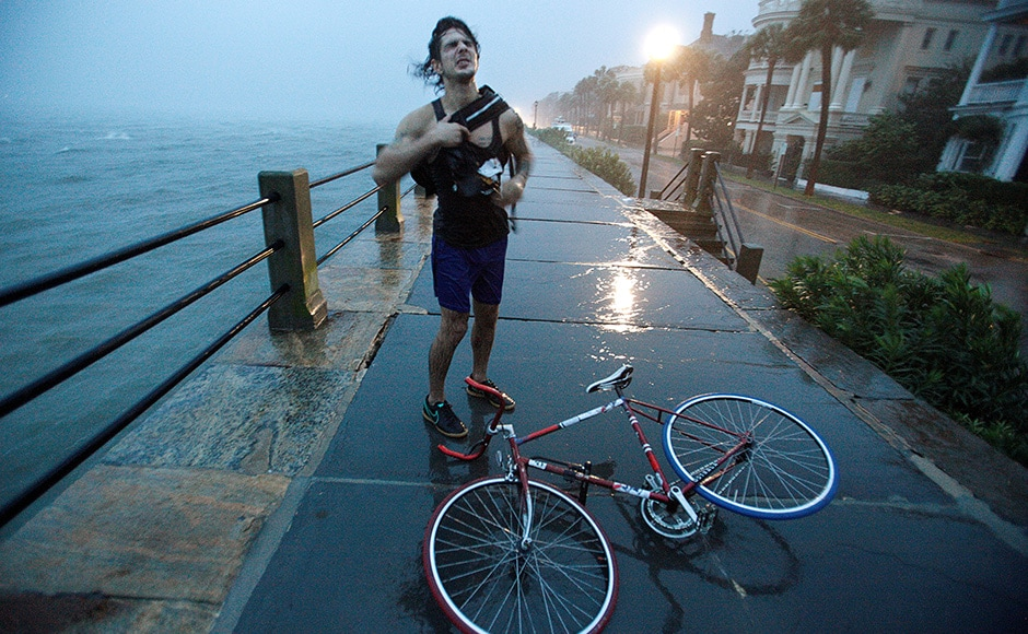 A Charleston resident reacts to the wind and rain as he pauses with his bicycle along the East Battery promenade on the southern tip of the city as Hurricane Matthew arrives in Charleston, South Carolina. Matthew triggered mass evacuations along the US Atlantic coast from Florida northward through Georgia and into South Carolina and North Carolina. Reuters
