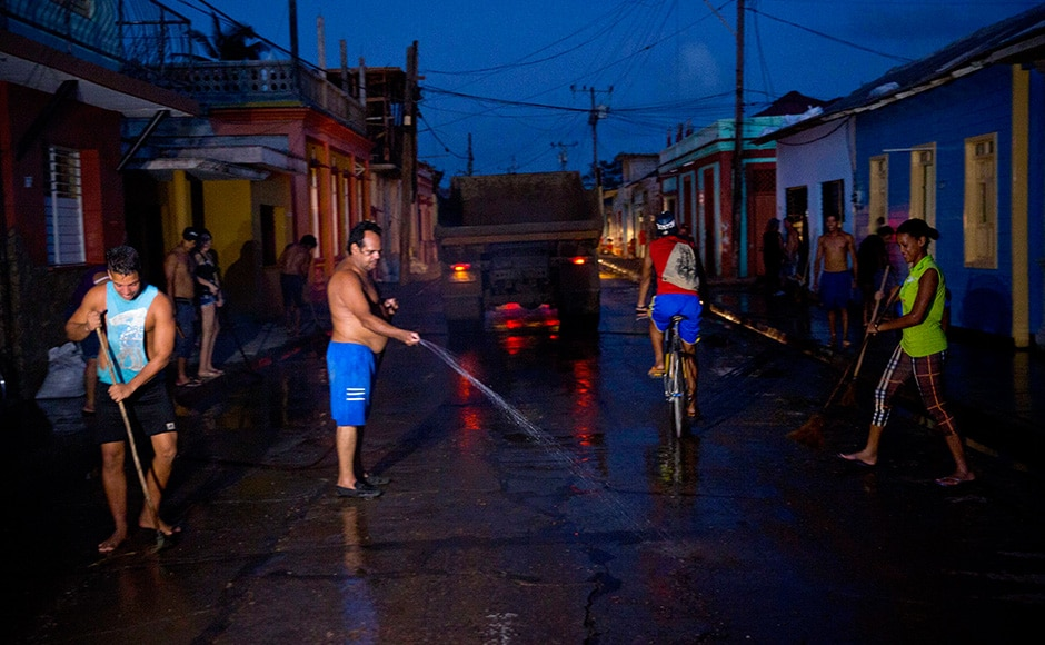 Residents clean a street muddied by the heavy rains brought by Hurricane Matthew in Baracoa, Cuba. Matthew hit Cuba's lightly populated eastern tip Tuesday night, damaging hundreds of homes in the easternmost city of Baracoa but there were no reports of deaths. AP
