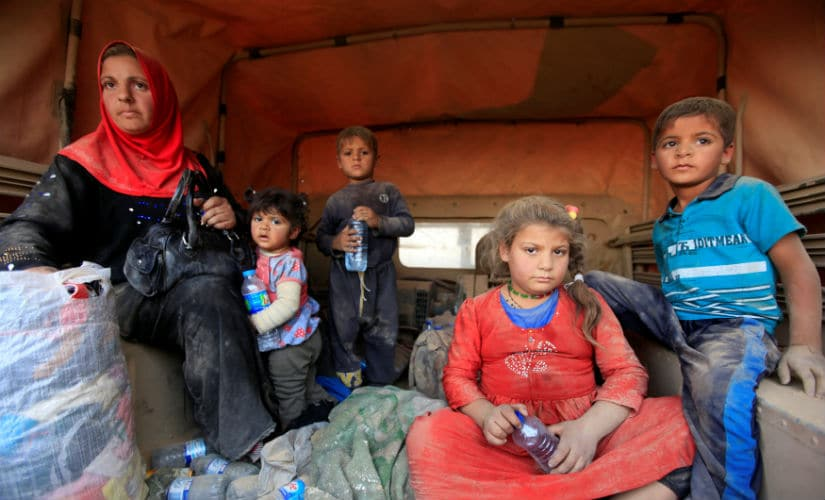 Displaced people who are fleeing from clashes sit at a military vehicle in Qayyarah during an operation to attack Islamic State militants in Mosul. Reuters