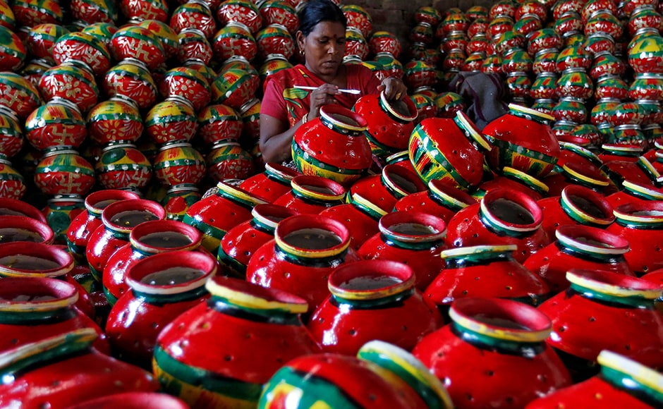 A woman decorates an earthen pitcher used during Garba  inside a workshop. During Navratri, feasting and fasting takes over normal life for millions of Indians, and many people join in religious dances in the evenings. Reuters