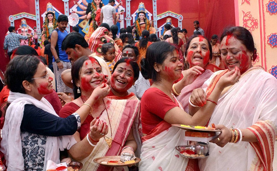 They also offered sweets to the god, and prayed for the well-being of their families and long lives of their husbands while performing these rituals. Married women participate in Sindur Khela during Durga Puja festival in Lucknow on Tuesday. (Photo: PTI)