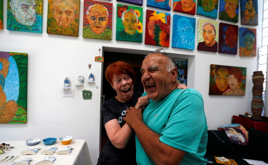 Artists Gonzalo Duran and his wife Cheri Pann laugh in the studio of their Mosaic Tile House. Image from Reuters
