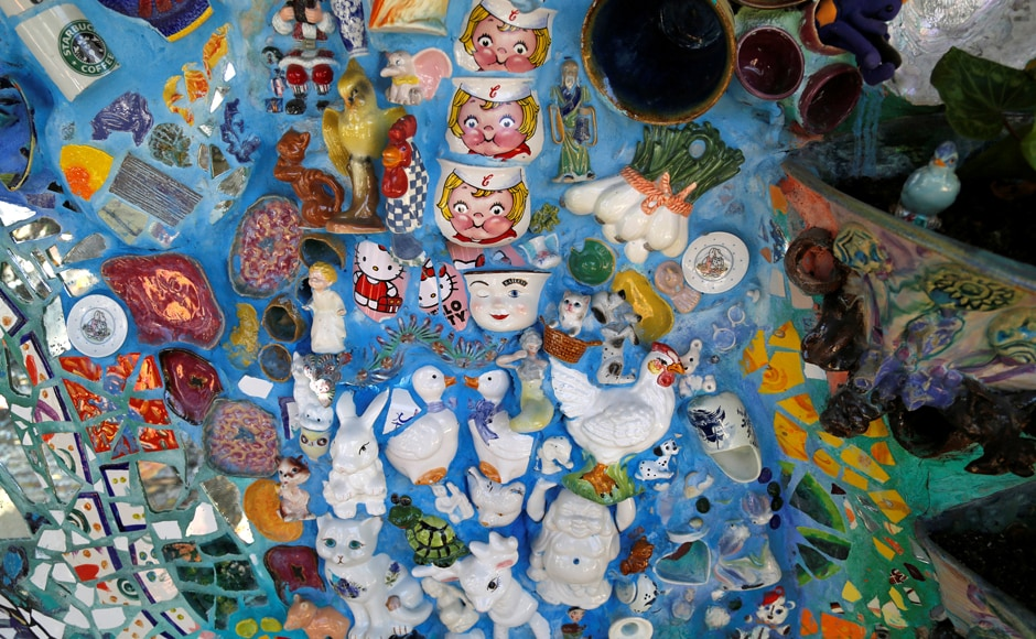 Coffee mugs and other objects are pictured cemented into a wall at the Mosaic Tile House. Image from Reuters