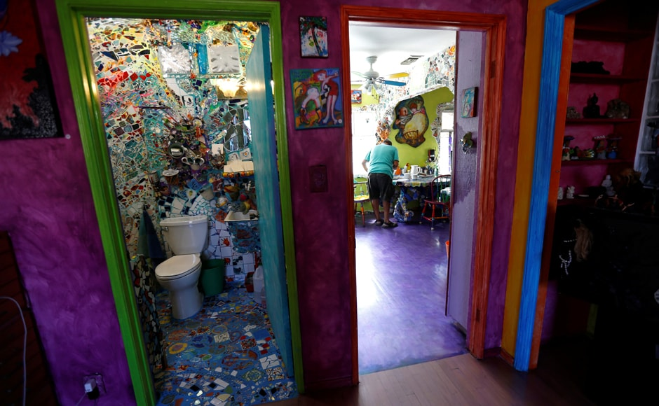 Artist Gonzalo Duran works in his kitchen as a bathroom is shown at his and artist Cheri Pann's Mosaic Tile House in Venice, California, US. Image from Reuters