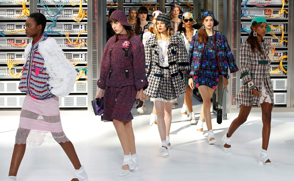 Models walking alongside rows of computer hardware wore classic Chanel tweed suits and jackets completed with metallic ballerina shoes. REUTERS/Charles Platiau