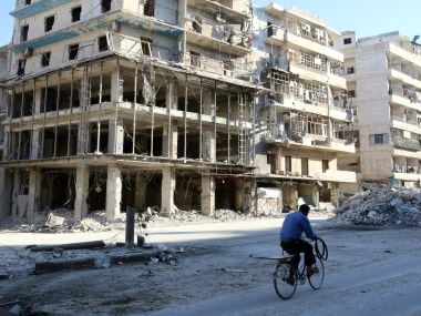 A man rides a bicycle near damaged buildings in the rebel held besieged al-Sukkari neighbourhood of Aleppo. Reuters