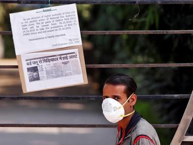 A private security guard wearing a mask stands next to a notice tied to a gate of the Deer Park which according to local media is temporarily closed to visitors as a precautionary measureafter ... birds died due to bird flu. Reuters