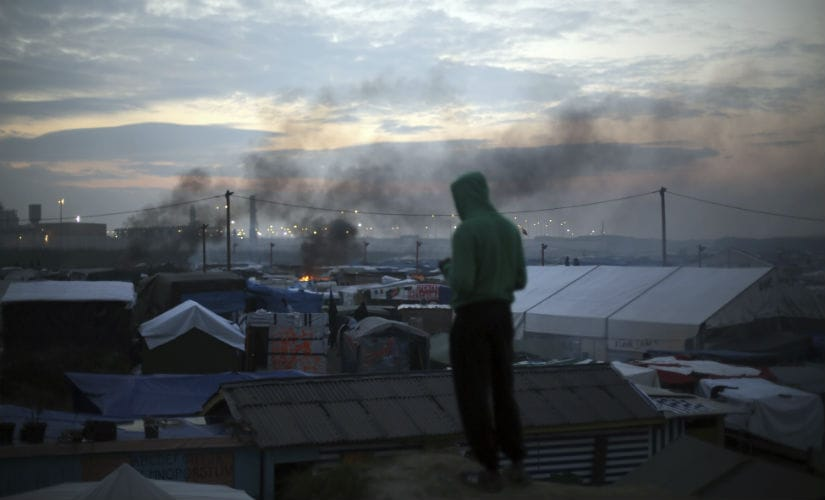 A migrant looks at the burning Calais camp. AP