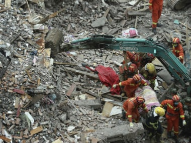 Rescuers take the bodies away from the debris. AP