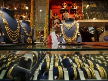 A saleswoman holds a pair of gold bangles while attending to customers at a jewellery showroom in Mumbai, India, July 21, 2015. To match GOLD-INDIA/DEMAND REUTERS/Shailesh Andrade - RTX1L7VN