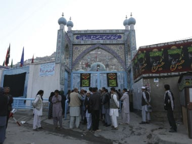 People stand infront of the shrine after the attack. AP