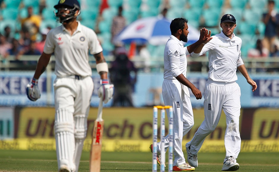 England's Adil Rashid, center, celebrates with teammate Joe Root the dismissal of India's captain Virat Kohli, left, on the fourth day of their second cricket test match in Visakhapatnam, India, Sunday, Nov. 20, 2016. (AP Photo/Aijaz Rahi)