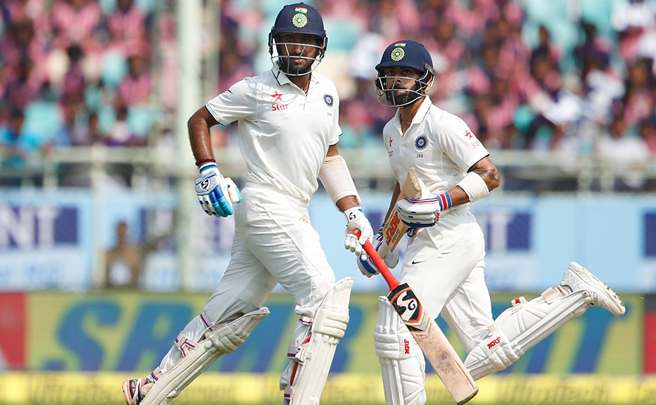 India's captain Virat Kohli, right, and Cheteshwar Pujara run between the wickets on the first day of their second cricket test match against England in Visakhapatnam, India, Thursday, Nov. 17, 2016. (AP Photo/Aijaz Rahi)