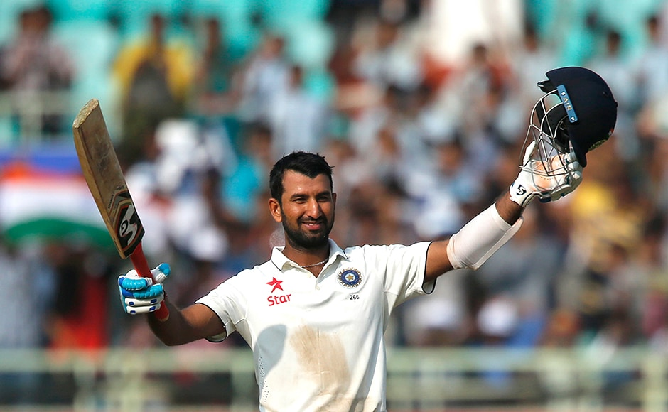 India's Cheteshwar Pujara raises his bat and helmet to celebrate scoring a century on the first day of their second cricket test match against England in Visakhapatnam, India, Thursday, Nov. 17, 2016. (AP Photo/Aijaz Rahi)