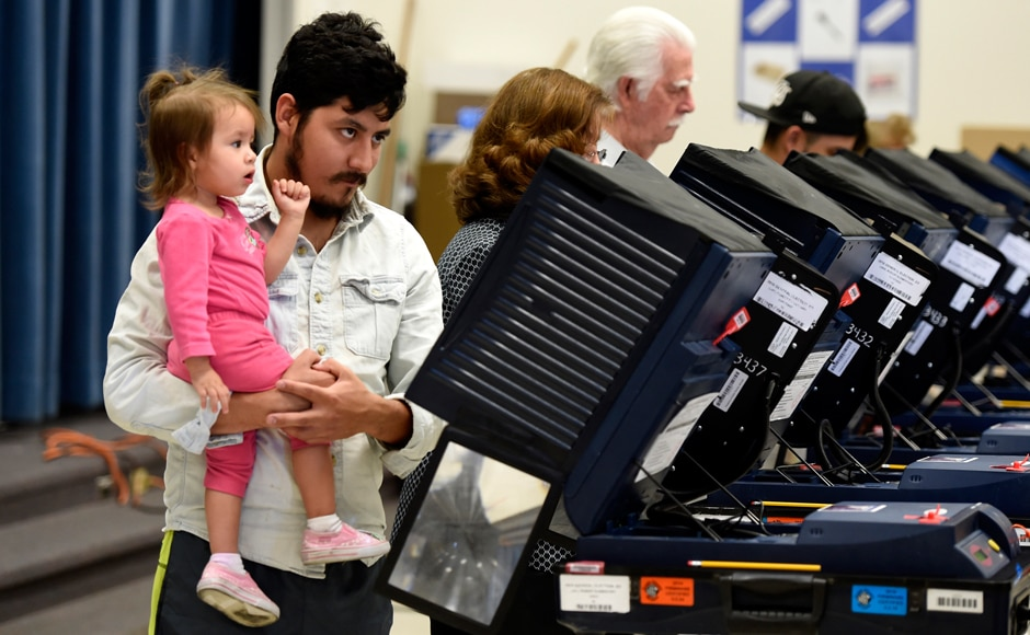 A man holds a young girl as he casts his ballot in Las Vegas, Nevada. Reuters