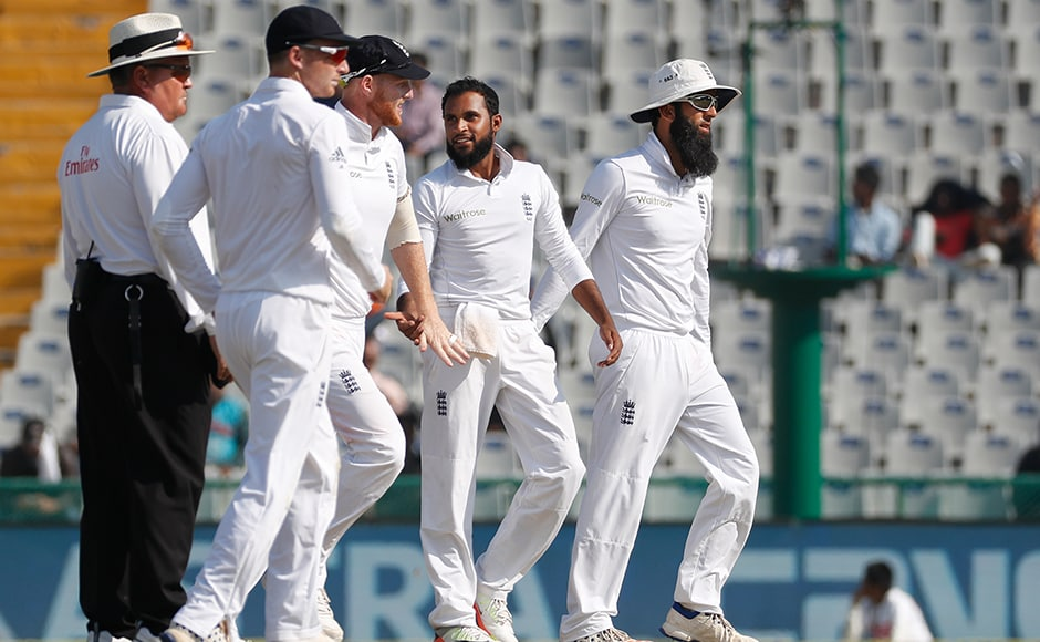 England's cricketers congratulate their teammate Adil Rashid (4-118) after taking the wicket of India's Ravindra Jadeja on the third day. (AP Photo/Altaf Qadri)