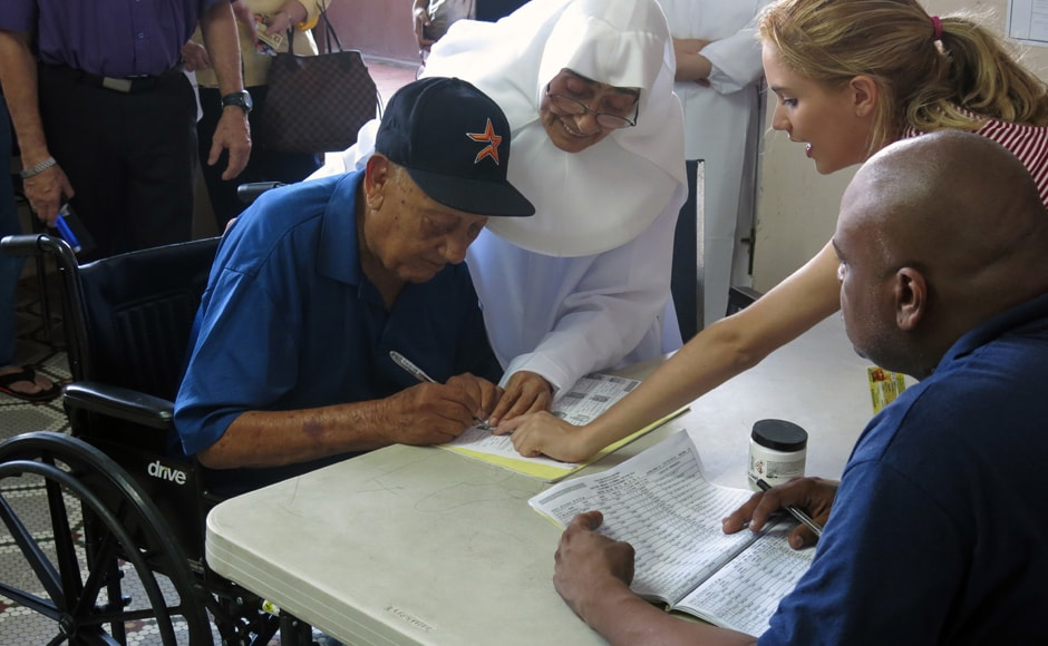 A voter signs in at a polling station to vote in the general election, at an elementary school in San Juan, Puerto Rico. Residents of Puerto Rico are US citizens, but they can't vote in the US presidential election, a fact that the leading candidate for governor wants to change. AP