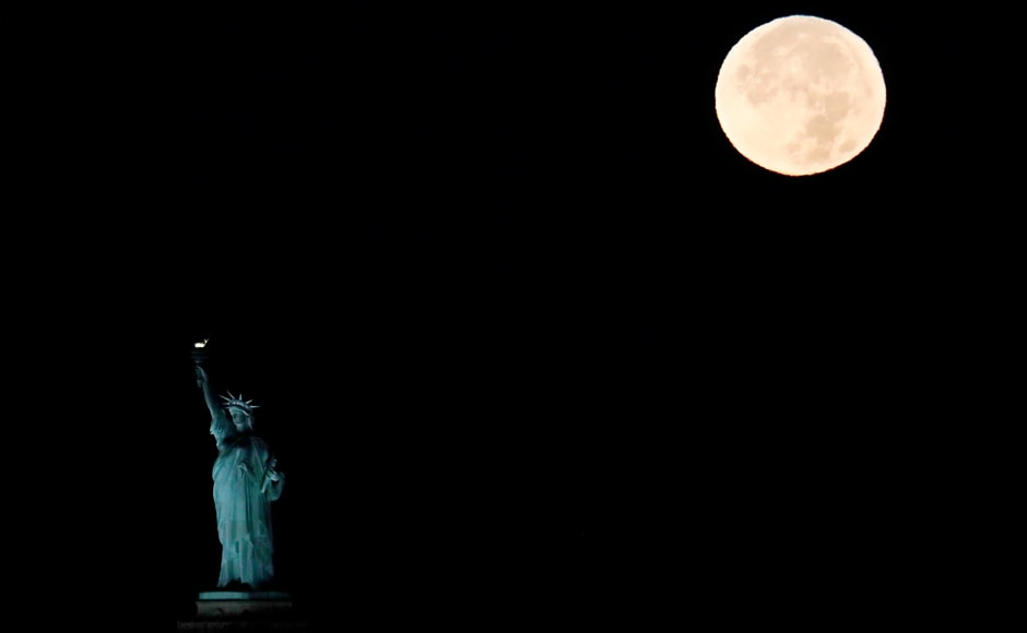 The supermoon sets behind the Statue of Liberty in New York. Monday's supermoon, a phenomenon that happens when the moon makes a close pass at the earth, is the closest to earth since 1948. AP