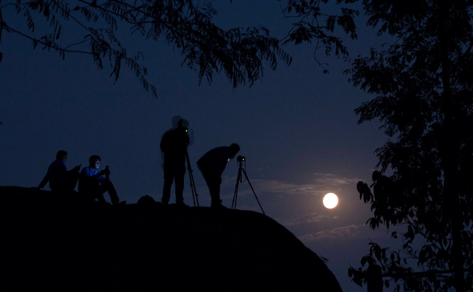 Tourists take photographs of the rising moon in Gauhati, India. AP