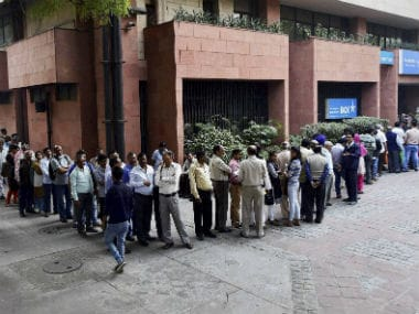 People queued outside an ATM. PTI