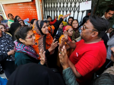 A file image of women arguing with a bank employee. Reuters