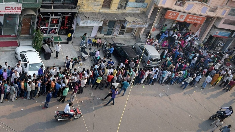 People queue up outside an ATM. PTI