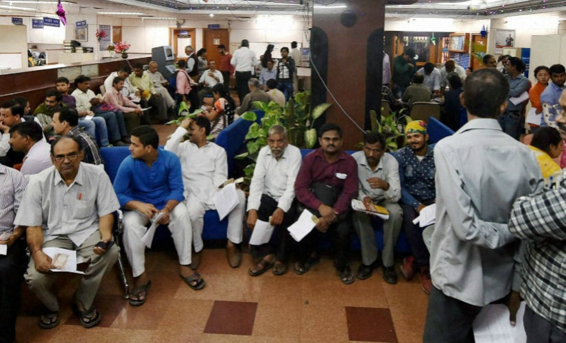 People wait to exchange their old Rs 500 and Rs 1000 notes and deposit cash at a Bank of India branch in New Delhi on Sunday. PTI
