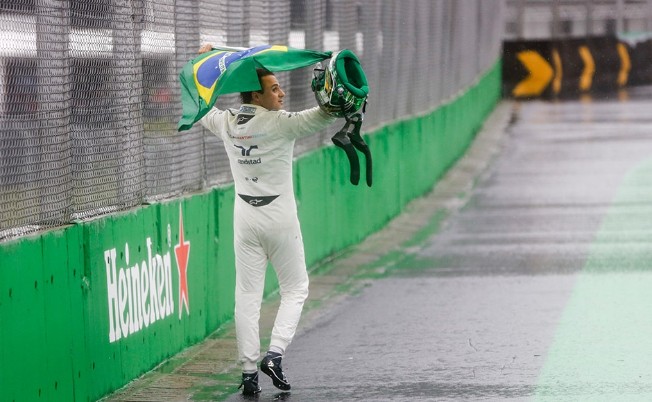 Felipe Massa walks on Interlagos with a Brazilian flag. His race came to a premature end after he careened into a barrier and lost control of his car. AP
