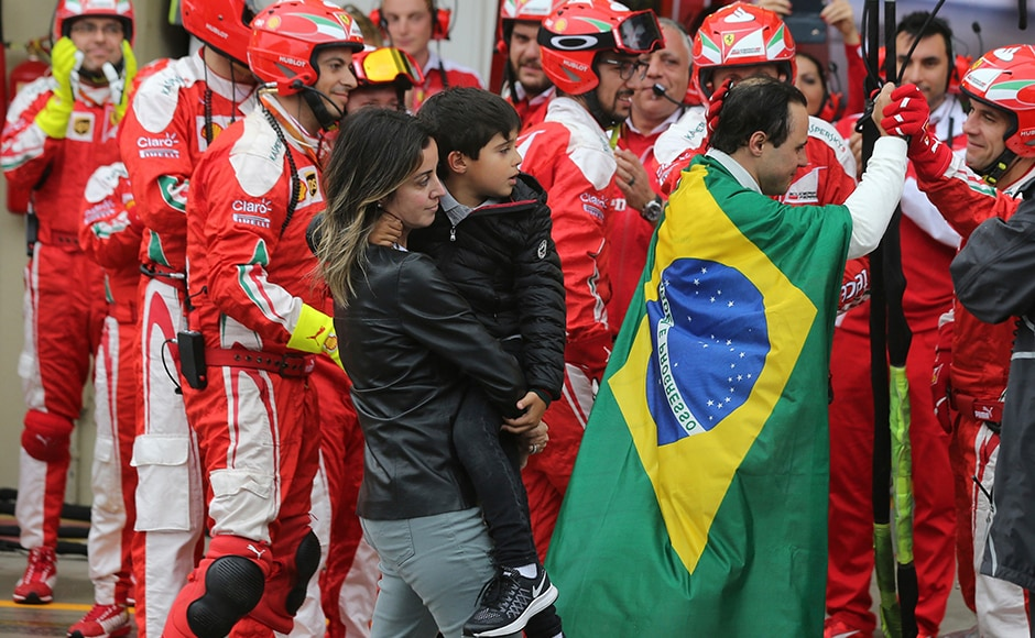 The Ferrari pit crew come out of their stations to give a guard of honour to Massa. AP