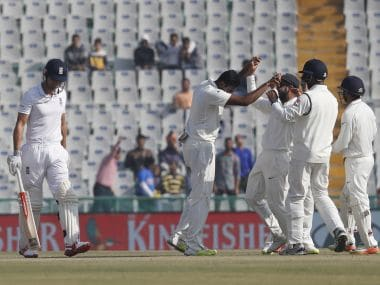 England's captain Alastair Cook walks back as Indian team celebrates his dismissal. AP