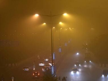 Vehicles ply on smog covered street in New Delhi on Saturday. PTI