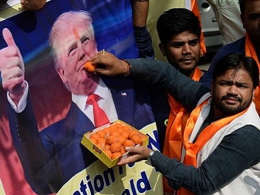 Right-wing activists of India's Hindu Sena offer sweets to a poster of US president-elect Donald Trump. AFP